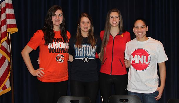De Soto High School seniors Kenna Hall, Brittani Jenson, Meredith Wolfe and Tori Marshall take a group photograph after signing their letters of intent on Feb. 4, 2015.