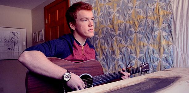 Simon Couch poses with his guitar on Jan. 25.