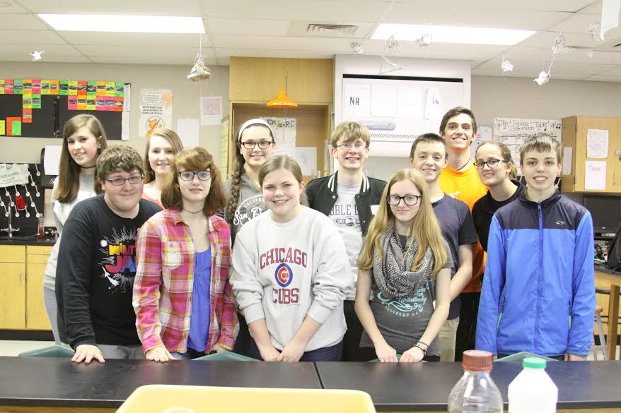 Science Olympiad team members line up and smile for the camera.
