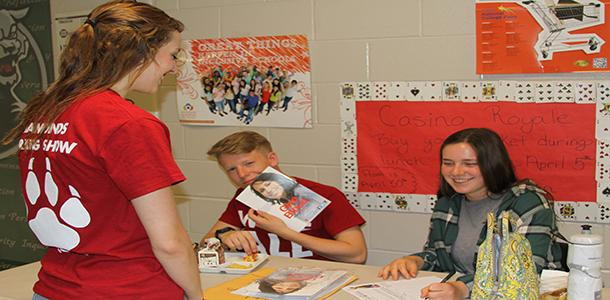 Senior Christa Stenzel being helped with blood drive sign ups by junior Taylor Ramseyer and freshman Alyssa Perry.