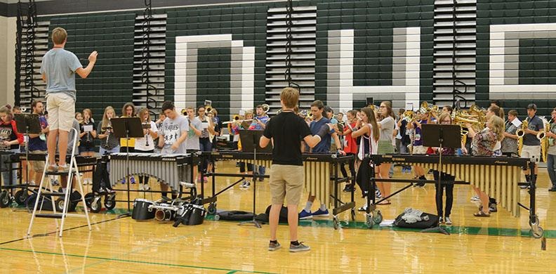 Drum majors Evan Sullivan and Zach Yarbrough conduct the De Soto High School marching band at rehearsal on Aug. 26.
