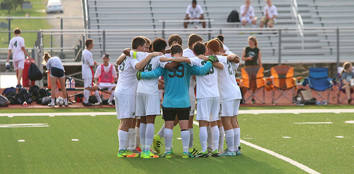 The varsity boys soccer starters huddle before the start of the game on Aug. 30.