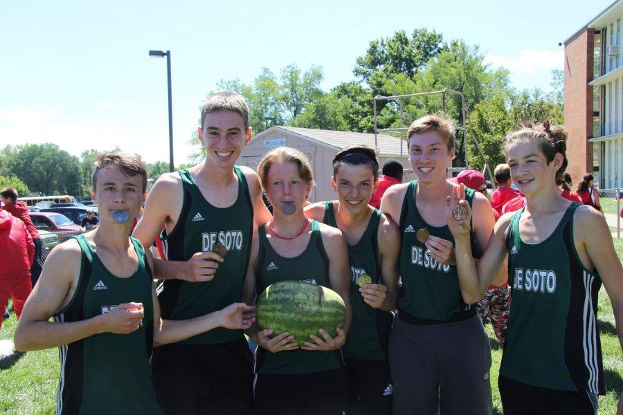 The boys varsity team poses with their medals and watermelon trophy on Saturday, Sept. 10 at Bishop Miege