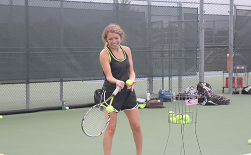 During a practice Zoller feeds balls to JV tennis players as they prepare for their upcoming match.
