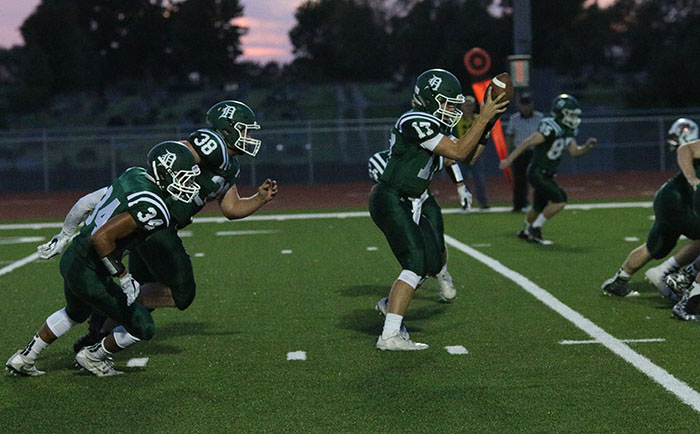 Junior quarterback Bryce Mohl receives a snap as running backs senior Mason Clark and junior Darren Winans anticipate the handoff.