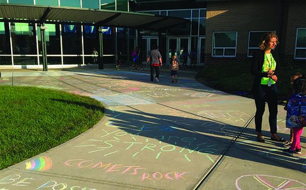 Starside students walk into school over the CatPRIDE members sidewalk chalk artwork for Peace Week. CatPRIDE students who volunteered included seniors Emma Bascom, Jackie Kennard and Kirstin Cuba, junior Sam McGuire and freshman Issa Sullivan.