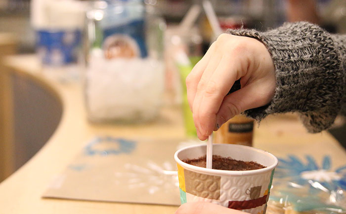 A student stirs his or her cup of hot chocolate on Tuesday, Dec. 13, as part of a fundraiser done by DHS marketing class.