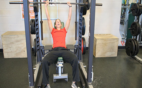 Physical education teacher Junelle Woolery lifts during her plan period on Dec. 8.