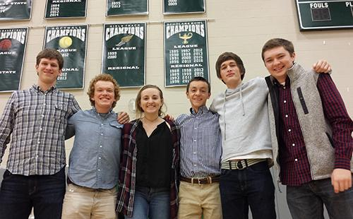 Seniors Dawson Field, Simon Couch, Mackenzie Smith, Ian Clouston, Trevor Whitlow and junior Cody Moose pose in front of the Scholars Bowl banner, with a freshly added '2016' under League champions.
