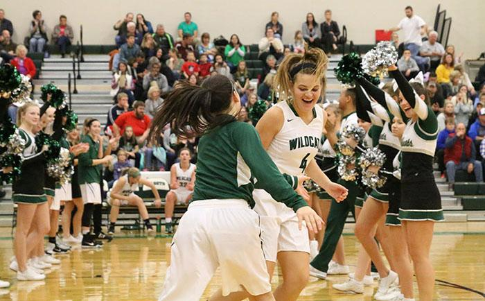 Juniors Mariah Grizzle and Mara Montgomery high five as they run onto the court for the DHS girls' home opener.