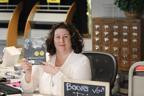 Head librarian and Books to Movies club director Jennifer Sosna holds up a copy of