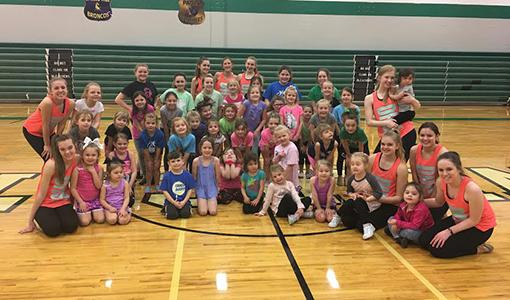 Junior dancers pose with the Diamonds after practicing at the junior dance clinic.
