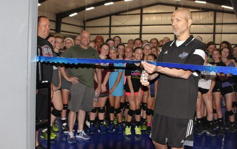 Mike Crist cuts the ceremonial ribbon at the end of the dedication of the Mike Crist Gymnasium on May 10 with Dynasty Volleyball coaches and players of all ages celebrating the occasion.