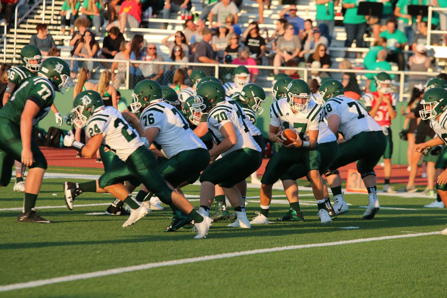 Senior+quarterback+Bryce+Mohl+receives+the+snap+as+the+offensive+line+springs+to+action.