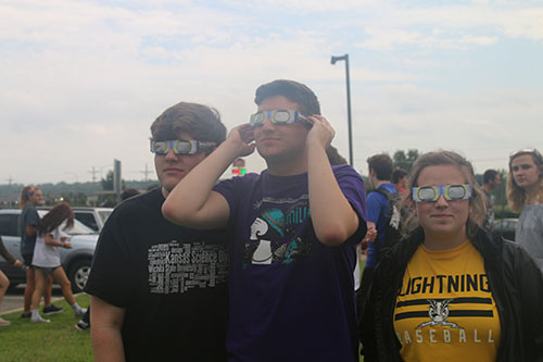 Seniors Micah Faulds, Johnny Meehan and Reaghan Wharff model their eclipse glasses on Aug. 21. Photo by Rylee Wilson.
