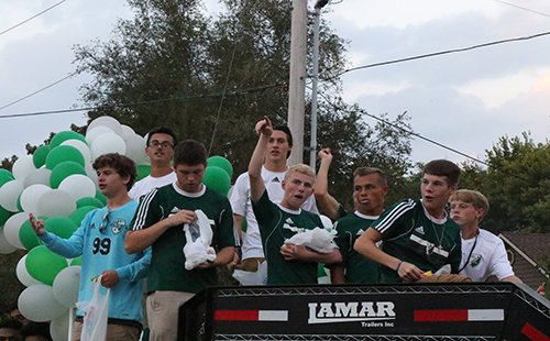 The De Soto High School varsity boys' soccer team cheer from the top of the soccer float on Sept. 20.