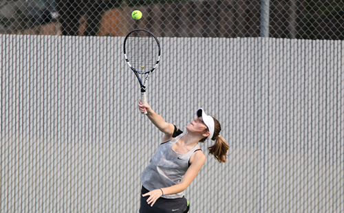 Junior Bailey Ramsdell serves to her opponent at Mill Valley during the tennis tournament.