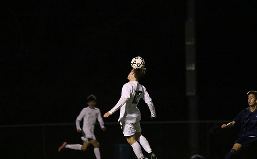 Sophomore James Henggeler heads the ball to pass it up the field on Oct 24.