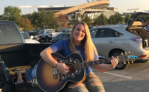 Senior Carly Newhouse plays her guitar outside of Kauffman Stadium.