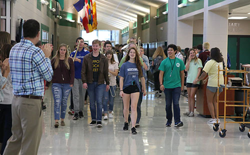 Freshman Molly Stack walks at the front of the gymnastics State sendoff on Oct. 19.