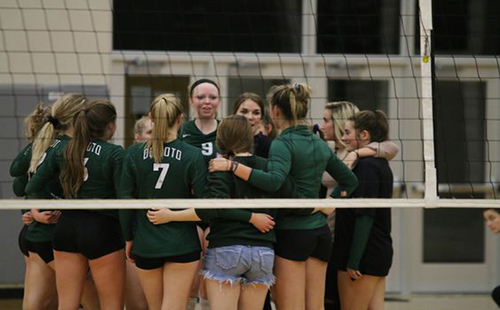 The De Soto High School varsity volleyball team huddles at a home game against Ottawa High School.