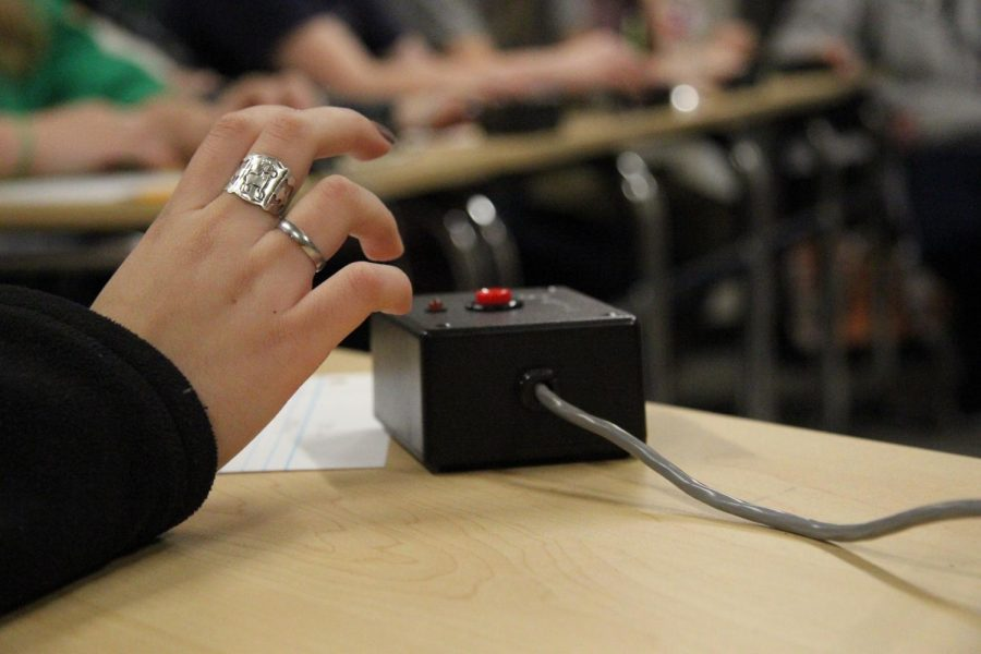 Junior Micaela Carillo's hand hovers over the buzzer in anticipation for the question at a scholars' bowl practice.
