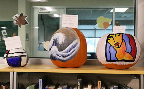 Student's pumpkins being displayed in the media center window.