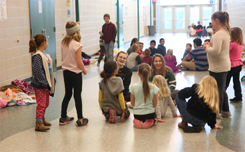 Juniors Lizzy Arnold and Caroline Whipple, both members of Student Council, laugh with Starside Elementary School students during the movie day hosted at DHS.