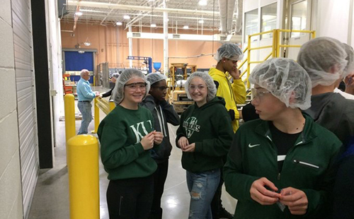 Sophomores Addison Gress and Katelyn Marti pose for a picture during a tour of the Huhtamaki facility while on a field trip for Business Essentials on Dec. 5.