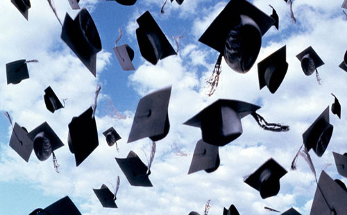 A group of graduates throw their caps into the air.