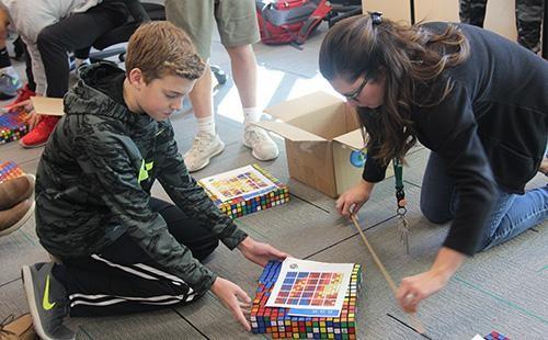 Freshmen Jake Facinelli works with teacher Inga Kelly to create Rubik's cube art on Dec. 2nd