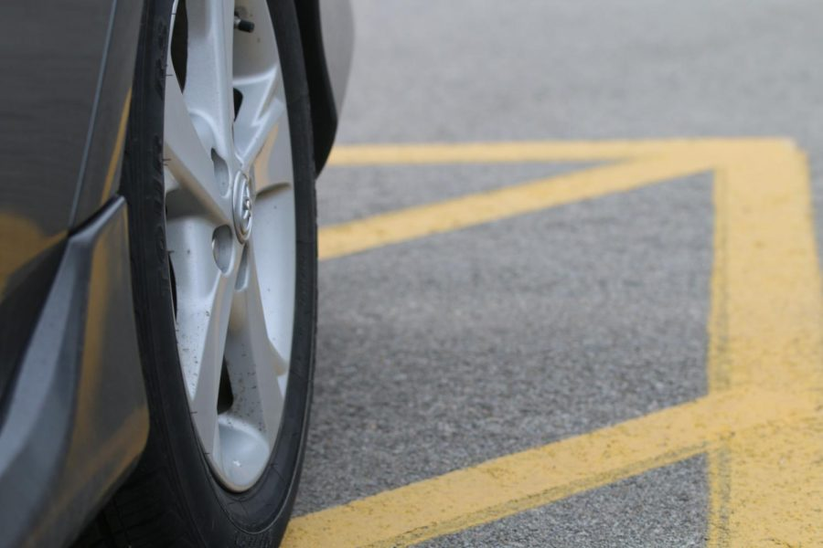 A car is parked illegally in a lined non-parking area during the school day at De Soto High School because there were no open spots on March 29.
