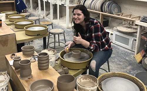 Junior Sam McCoy, who is interested in minoring in art, poses while in the progress of throwing on the potter's wheel at the University of Kansas on March 2.