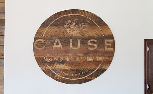 A handmade wooden sign displaying the shop's logo adorns the front wall of Cause Coffee.