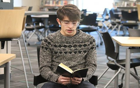 Junior Matthew Jones reads a poem he wrote to the Poetry Slam group in the media center during seminar on April 19.