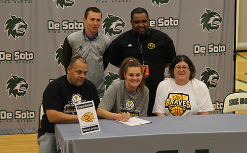 Surrounded by family and coaches, senior Mariah Grizzle signs her national letter of intent to play college basketball at Ottawa University on April 30.