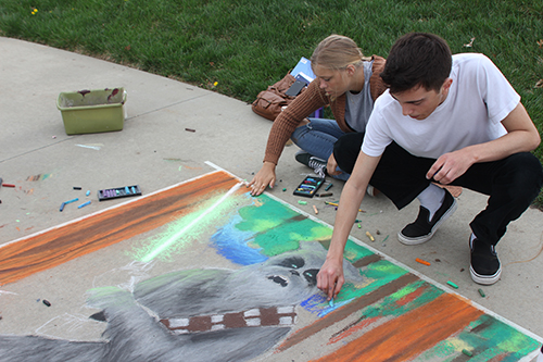 Seniors Sam McGuire and Carly Bodenhausen work on the background of a sidewalk chalk drawing for the Frontier League art show. The theme was to turn the school's mascot into a Jedi Knight.