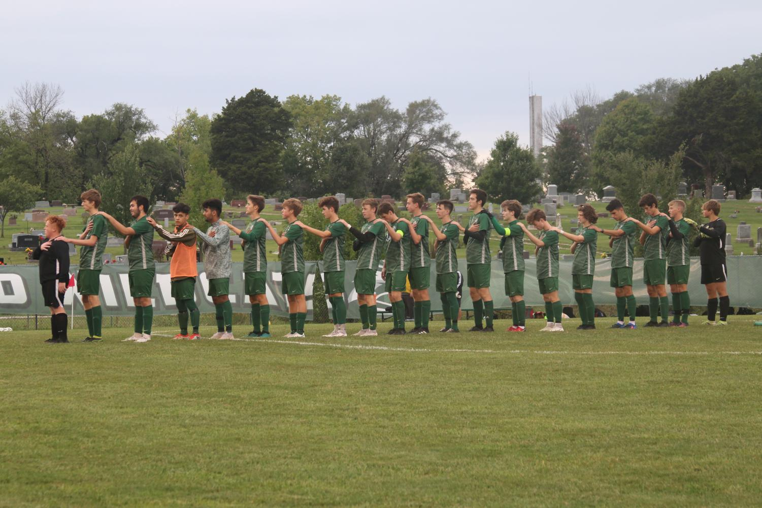 The+boys%27+soccer+roster+lines+up+at+midfield+for+the+National+Anthem+prior+to+their+game+against+Basehor-Linwood+on+Sept.+25.