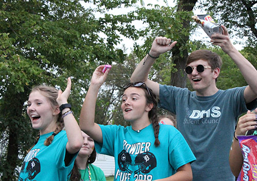 Juniors Corinne Daise, Maddy Mascareno and Colton Jones throw candy out to the crowd in downtown De Soto during the homecoming parade on Sept. 12th.