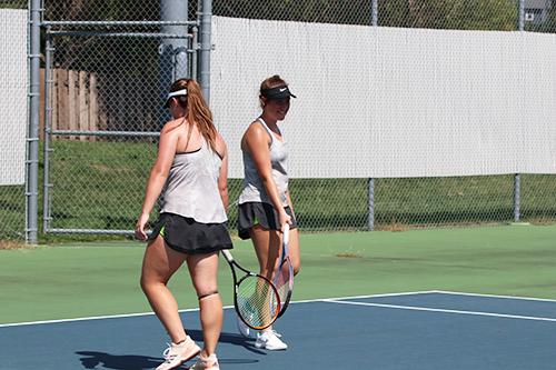 Sophomores Jenna Doran and Hallie Scott encourage each other in between serves on Sept. 15.