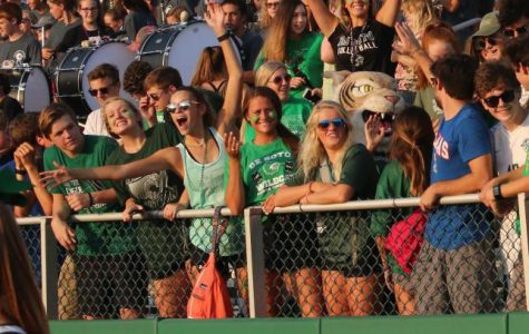 Senior Dravhen Moore stands in the student section with her arms in the air as she cheers on the football team at the Fall Festival on Aug. 2