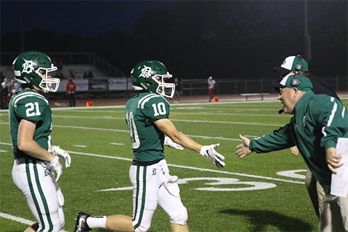Sophomore Tyson Priddy (left) and senior Keegan Sturdy (right) run to high-five coach Brian King at the game against Wyandotte High School on Sept. 7.
