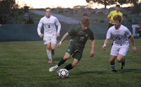 Junior forward James Henggeler dribbles past a Basehor-Linwood defender at the home soccer game on Sept. 25.