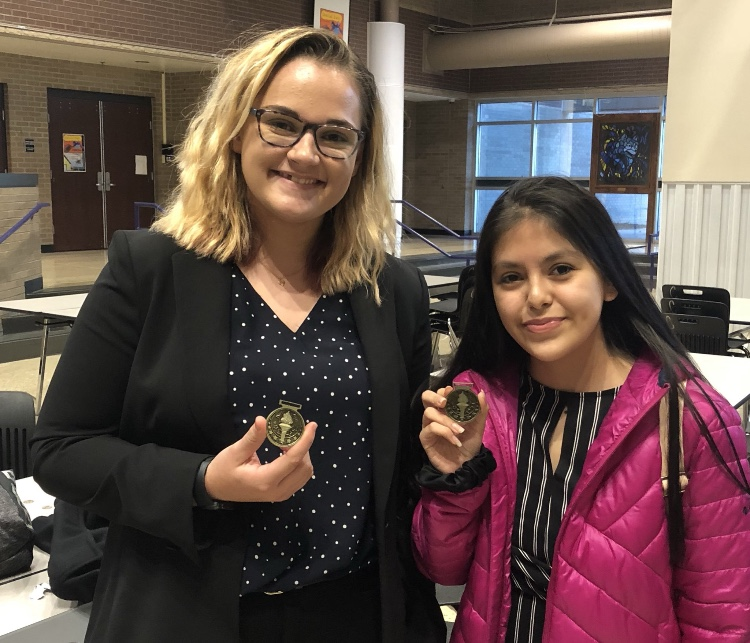 Junior Kate Tickle and freshman Deleana Marquez pose with their fourth-place medals at the Blue Valley Northwest novice debate tournament on Oct. 20.