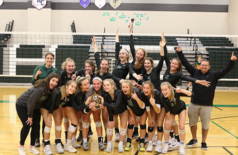 The De Soto High School varsity volleyball team celebrates after defeating Lansing to win the championship game at Spikefest on Oct. 5.