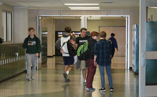 Sophomore students socialize in the hallway before leaving for grade check early release.