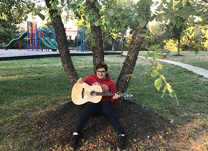 Sophomore Adam Kellogg poses with his guitar.