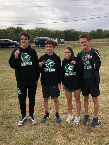 Freshman Katelyn Gress shows off her cross country medal along with her teammates at the Topeka-Seaman meet on Sept. 29, 2018.