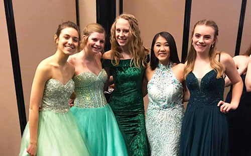 A group of De Soto High School students show off their dresses backstage of the Natalie M. Fashion Show on Feb 3.