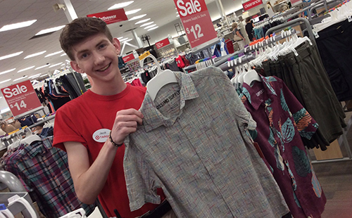 Senior Jacob Ward, who works as a style consultant at the Target on Shawnee Mission Parkway holds up a shirt from the men's section on June 17.